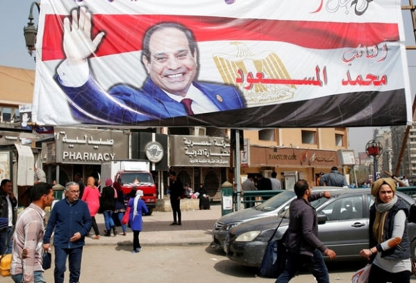 People walk by a poster of Egypt's President Abdel Fattah al-Sisi for the upcoming presidential election, in Cairo